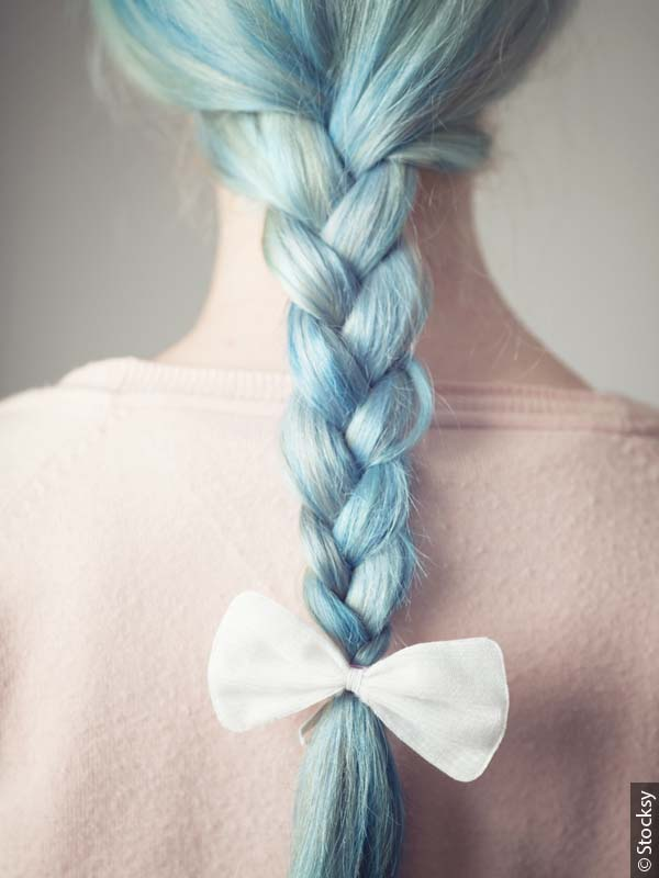 Back view of a woman with a pastel blue braid accessorized with a white bow.